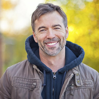 Man outdoors smiling - dental implants