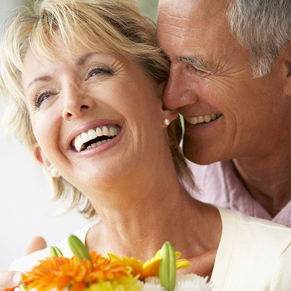 Older couple touching faces and smiling - restorative dentistry