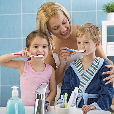 Dentist Highlands Ranch - mother helping two kids brush